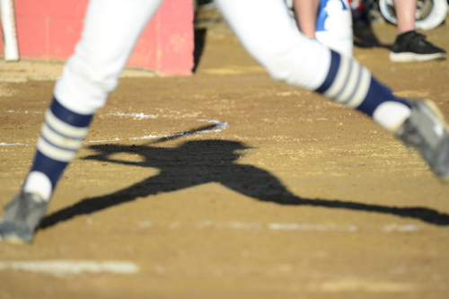 The setting June sun casts a shadow of a McDevitt hitter. The Crusaders had nine hits against Hamburg in the district final.