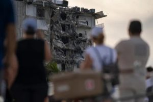 People watch the partially collapsed Champlain Towers in Surfside, Florida, north of Miami Beach.
